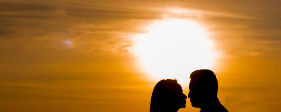 ragazza cinese e uomo che si baciano al tramonto